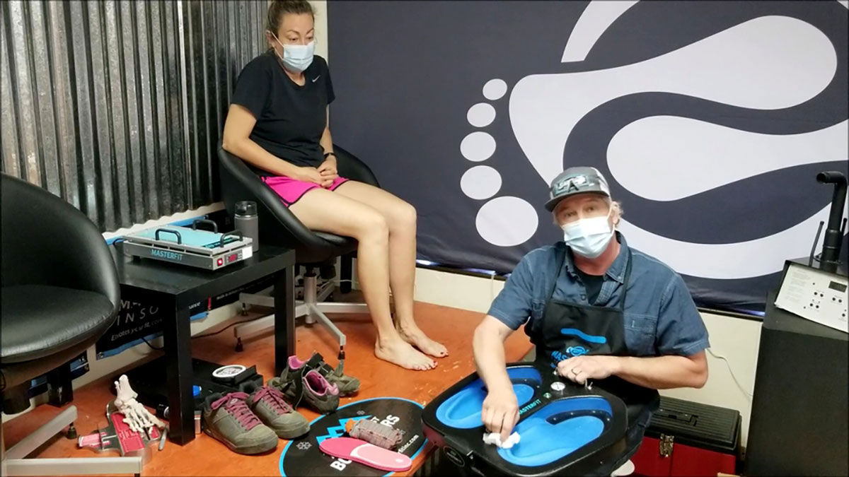 Bootfitter with mask in shop